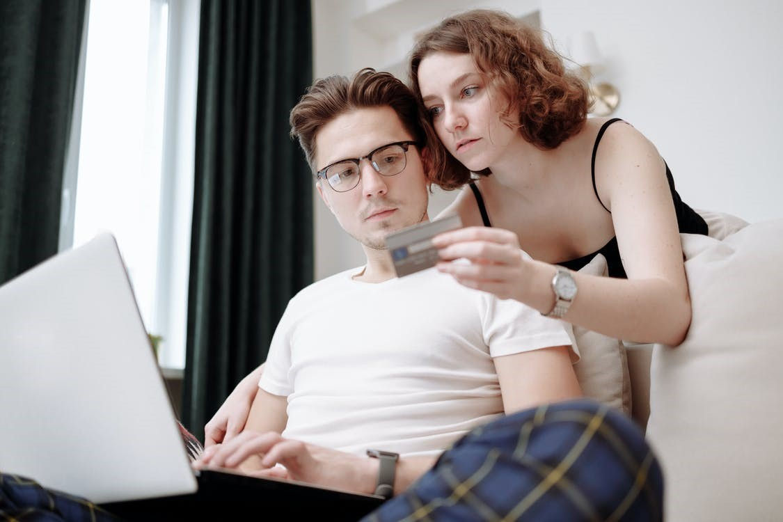 A couple uses a credit card to make online purchases while looking somber